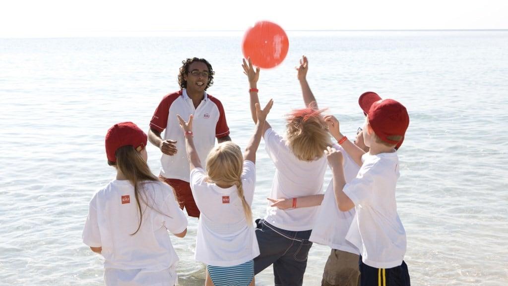 Un grupo de niños jugando en la playa con uno de nuestros monitores