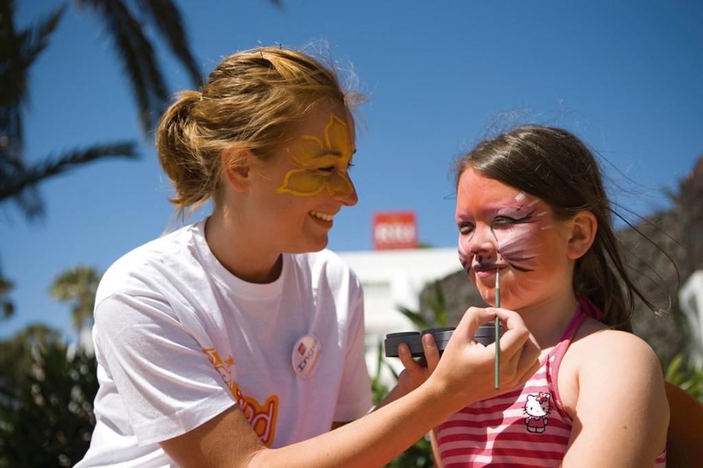 Una monitora del equipo pintando a una niña